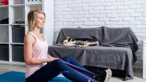 Mulher sentada em uma esteira de treino fazendo exercícios com elástico