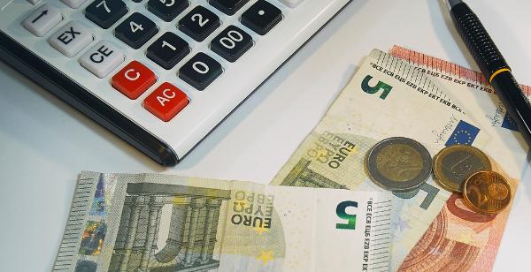 Notas de dinheiro ao lado de uma caneta e uma calculadora